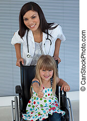Young female doctor and Smiling girl on a wheelchair with thumb up in the hospital