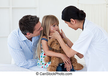 Female doctor examining little girl accompanied by her...