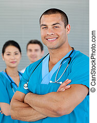 Ethnic doctor with his colleagues in the background. Medical...