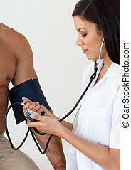 Close-up of a female doctor checking the blood pressure of a...