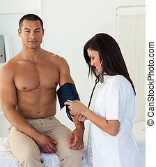 Smiling doctor checking the blood pressure of a patient