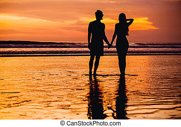 Silhouettes of young couple in love staing on the beach with...