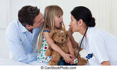 Doctor examining child\'s throat during a check-up
