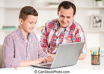 Father and son at home - Father and son using laptop...