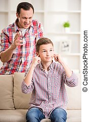 Father and son at home - Son closing ears while father...