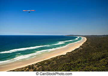Hanging Gliding Along beach in Byron Bay Australia - Hang...