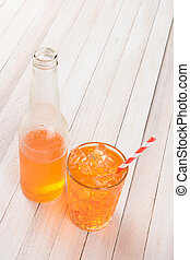 Orange Soda Bottle Glass and Straw - HIgh angle shot of a...