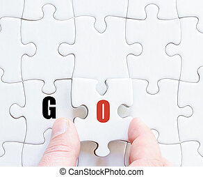 Last puzzle piece with motivational word GO - Hand of a...