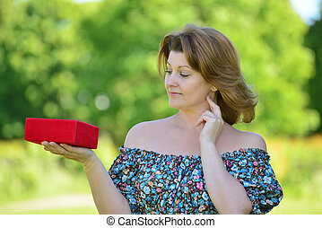 Cute woman with gift at summer park