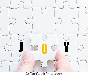 Last puzzle piece with motivational word JOY - Hand of a...