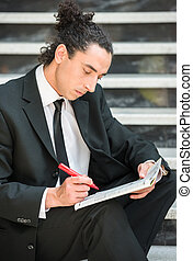 Unemployed man - Man in suit sitting at stairs with...
