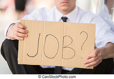 Unemployed man - Close-up of man in suit holding sign in...