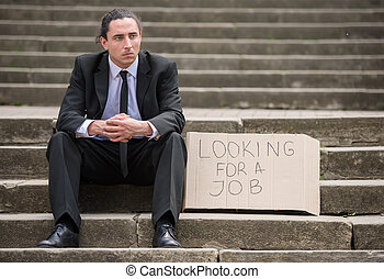 Unemployed man - Man in suit sitting at stairs with sign....