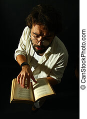 expressive man reading a book on black background