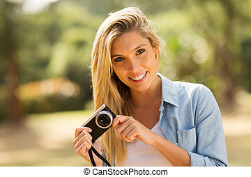young woman holding a camera at the park