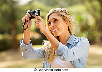 blonde woman taking picture with camera