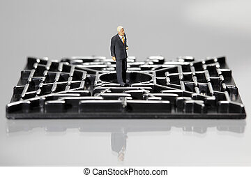 Businessman in a labyrinth - Business figurine standing in...