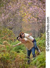 Happy joyful couple having fun piggybacking laughing...
