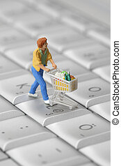 Online shopping - Miniature shopper with shopping cart on a...
