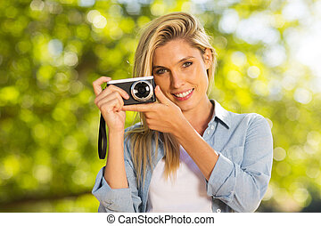 blond woman with a camera outdoors - smiling pretty blond...