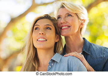 senior mother and young daughter looking up - smiling senior...