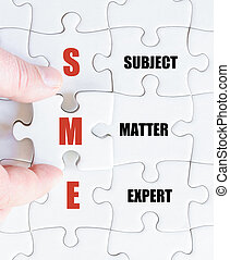 Last puzzle piece with Business Acronym SME - Hand of a...