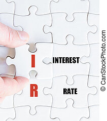 Last puzzle piece with Business Acronym IR - Hand of a...