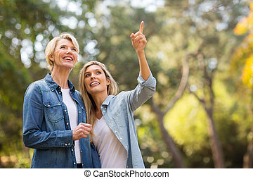 young daughter taking middle aged mother for a walk