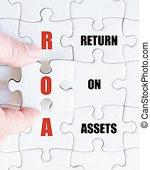 Last puzzle piece with Business Acronym ROA - Hand of a...