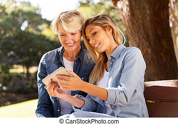 young daughter using smart phone with mid age mother -...
