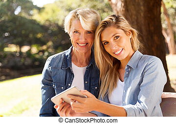 mother and daughter using smart phone - portrait of pretty...