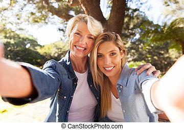 senior woman and daughter taking selfie - happy senior woman...