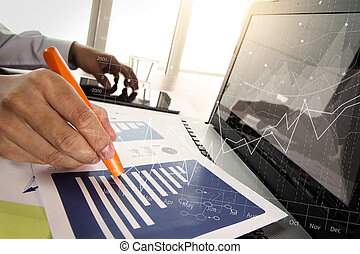 business documents on office table with smart phone and digital tablet with laptop computer and man working in moment