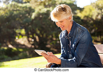 senior blond woman texting on smart phone