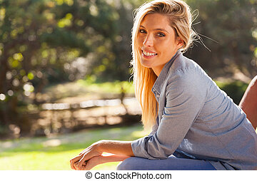 young blond woman sitting at the park