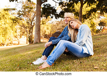 mother and adult daughter sitting on grass