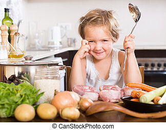 Happy child cooking soup at home kitchen
