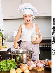 baby girl in cook hat cooking soup in kitchen