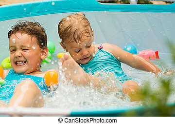 Children swimming in kid pool - Happy children having fun in...