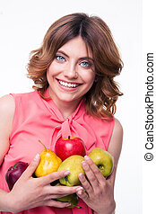 Smiling beautiful woman holding fruits isolated on a white...