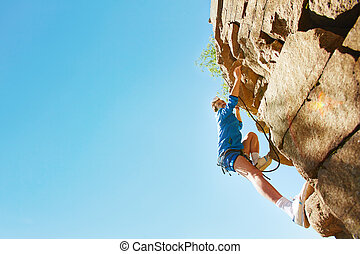 Adventurous hiker - Young man in activewear climbing the...