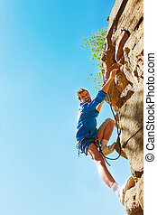 Mountain climber - Young mountain climber reaching top of...