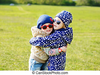 hugging girls - two little girls are hugging in spring field