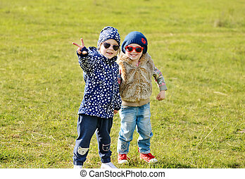 cute friends - two little girls are playing in spring field