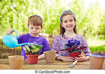 Cute friends gardening - Two youngsters taking care of...