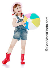 Cheerful girl in short summer shorts and boots holding a...