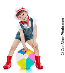 Cheerful girl in shorts, hat and rubber boots playing...