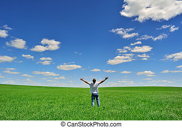 man on the field under beautiful sk - man with arms raised...
