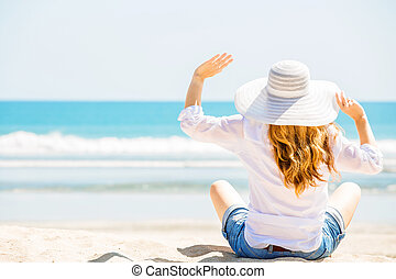 Beautifil young woman sitting on the beach at sunny day...