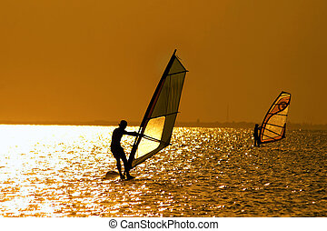 Two windsurfers - Silhouettes of two windsurfers at the...